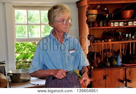 Mystic Connecticut- July 11 2015: Docent holding a stalk of Rhubarb giving a cooking demonstration in the 1768 Buckingham-Hall House kitchen at Mystic Seaport