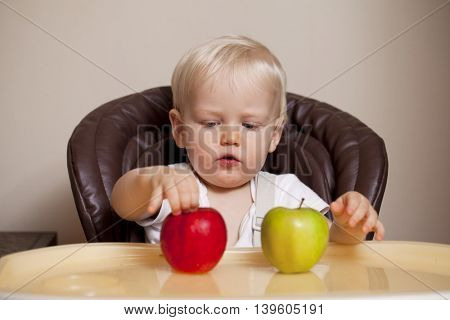 Portrait of blonde baby boy sitting at the dinner table