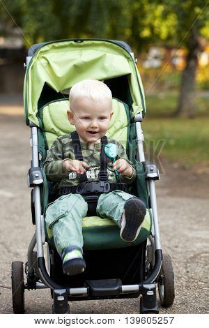 Little boy sitting in stroller in summer park