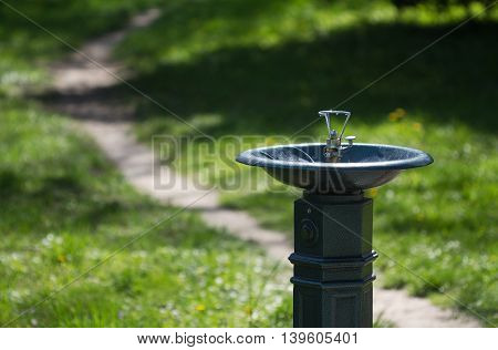 Horizontal close up of a metal water dispenser in a green park