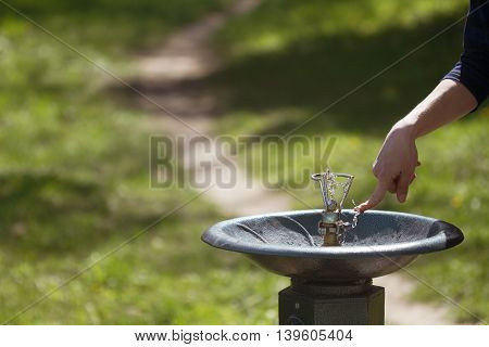 Horizontal close up of a hand pushing a metal water dispenser in a green park