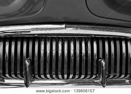 A close up abstract view of the front grill on an old scrap car