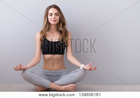In harmony with mind. Pleasant relaxed woman sitting on the floor and closing her eyes while practicing yoga
