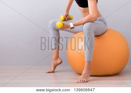 Stay in shape. Pleasant slim woman sitting on the rubber ball and using dumb bells while doing sport exercises