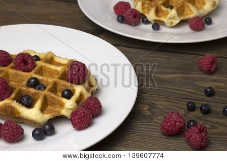 two plates of waffles with berries on the table , blueberries, raspberries and a cup of tea delicious breakfast