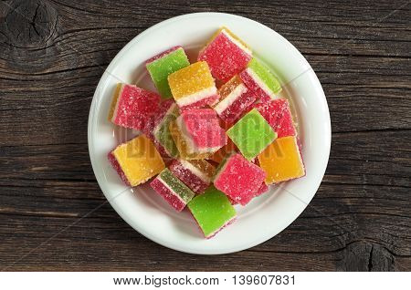 Colorful jelly candies in plate on dark wooden background top view