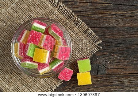Colorful jelly candies in glass bowl on dark wooden background top view