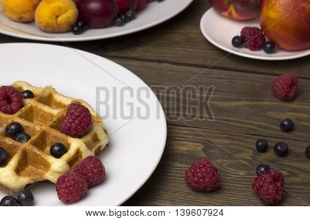 Two plates of waffles and berries raspberries and blueberries , apricots and peaches on a wooden table