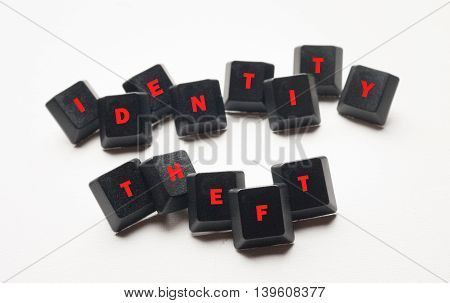 Identity theft text in red on black computer keys.White background