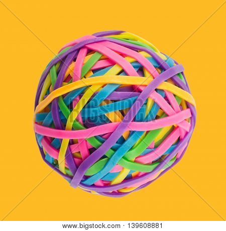 Rubber elastic band ball on light yellow background