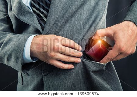 Businessman putting a gift-box in the pocket