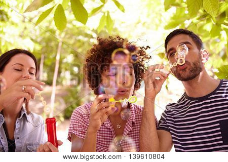 Three Happy Young Friends Blowing Bubbles