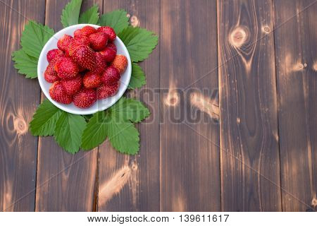 Strawberries in plate on wooden table top view