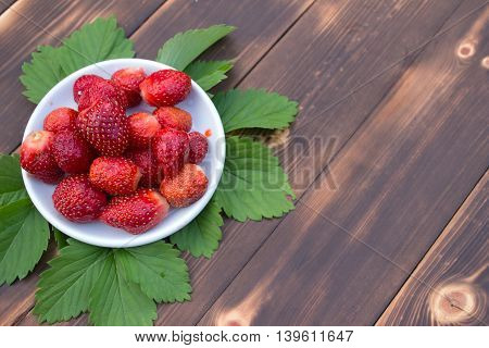 Fresh juicy strawberry isolated on a wooden table. top view