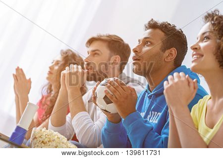 Let have another round. Close up of african man holding soccer ball in his hands and supporting football on TV with friends