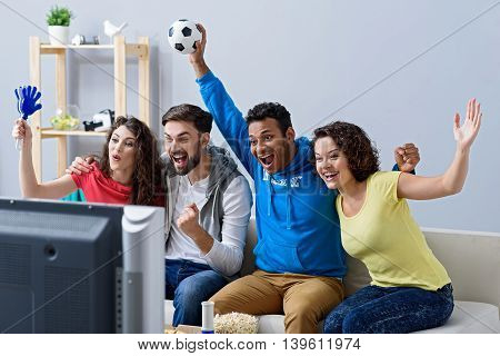 Sunday sports. Group of happy sports fans watching game on TV at home and holding soccer attributes