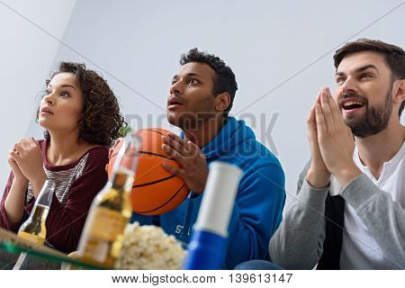 We need goal. Close up of shocked friends from different country watching basketball match on TV isolated on white background
