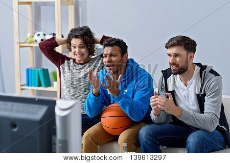 How could it happen. Group of friends watching bad basketball game on TV with expression because their team lost