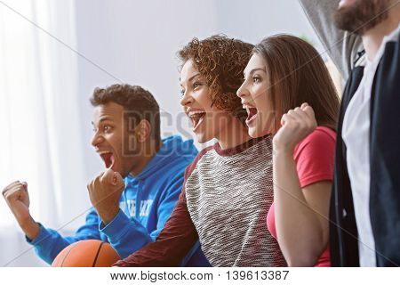 This is our victory. Close up of smiling friends watching television in living room and cheering on their favourite team