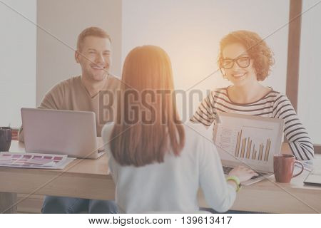 Professional team. Smiling and delighted young managers sitting at the table, using laptops in the office and drinking coffee