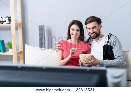 Carefree relaxed lifestyle. Smiling couple sitting at home on couch, watching TV and eating popcorn