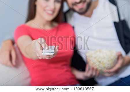 Technology in hand. Close up of girl hand holding TV remote with guy sitting next to her with popcorn