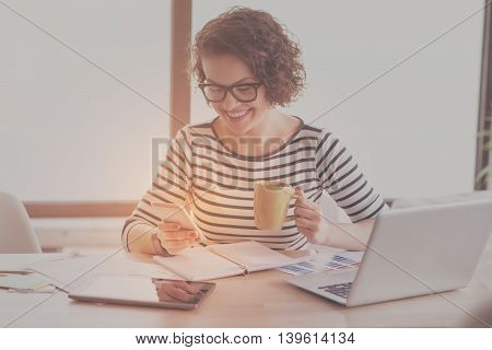 Involved. Positive and content young businesswoman using smart phone and holding cup of coffee while sitting at the table