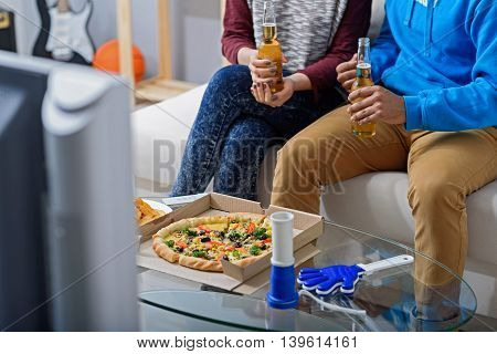 Right preparation for watching match. Close up of pizza on table next to football attributes with couple holding beer in background