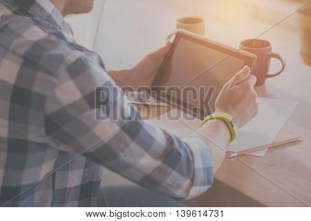 Using technologies. Cropped image of man using digital tablet