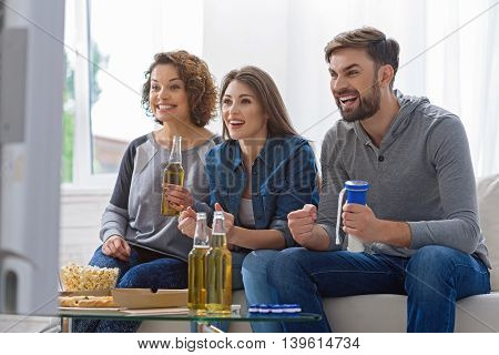 They are real fans of football. Cheerful group of friends watching football game on tv, sitting on sofa near window