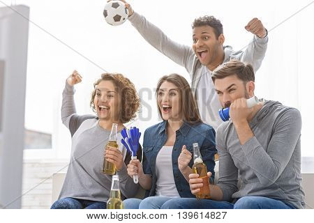 Football is their great common passion. Screaming group of young football fans watching television with beer and soccer attributes