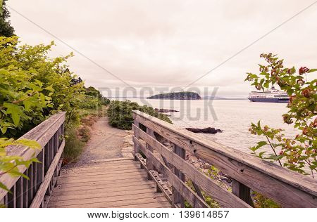 Toned image of ocean path in the town of Bar Harbor Maine and cruise ship in the distance.