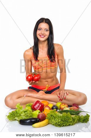 Portrait of slim fitness cheerful girl sitting in studio with set of fruit and vegetables over white background. Healthy eating, diet, fitness, weight lose concept.