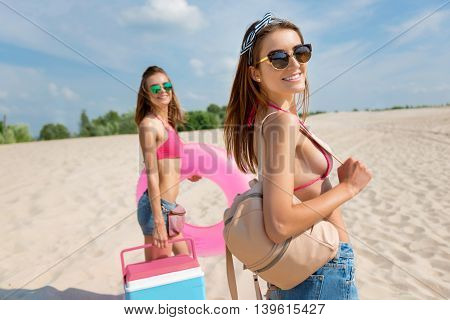 Want some fun. Cheerful young women smiling and standing on the beach while going to the seaside
