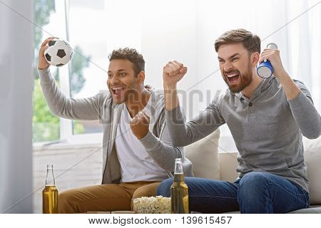 This is sport only for men. Cropped photo of two excited soccer fans watching tv at home with window in background