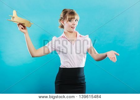 holidays and tourism concept. attractive woman airplane stewardess invites to travel holding paper toy airplane in hand