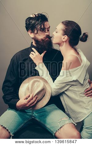 young sexy couple of woman with glamour makeup on pretty face in stylish shirt and bra kiss handsome bearded man with long beard and wet hair holding straw hat in studio on grey background
