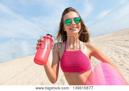Ready for a great day. Cheerful delighted woman holding inflatable ring and drinking water while resting on the beach