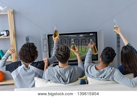 Good times together. Rear view of four football fans celebrating victory of favorite team, holding beer bottles in their hands