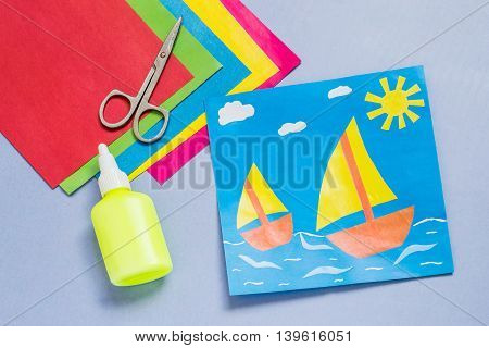 Paper applique is made by the child on a sea theme with sailboats. The idea for children's creativity an art project made of paper. Sheets of colored paper glue scissors