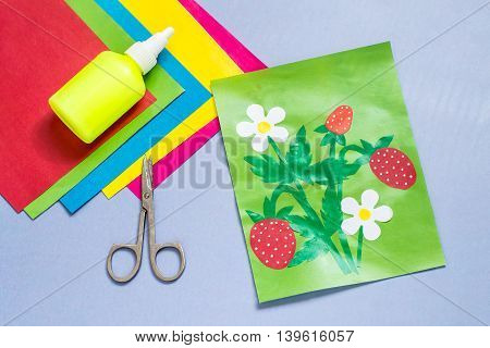 Paper applique is made by the child on a summer theme with strawberries. The idea for children's creativity an art project made of paper. Sheets of colored paper glue scissors