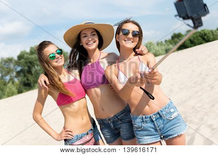 Sweet memories. Joyful smiling delighted friends bonding to each other and making selfies while resting on the beach