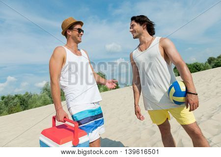 Nice talk. Cheerful delighted friends talking and standing on the beach while resting together