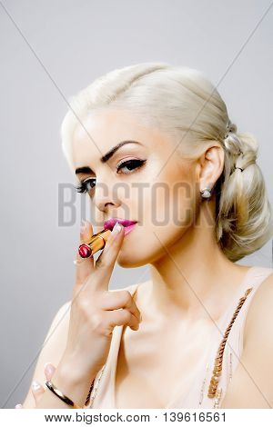Young woman with pretty face blonde hair and glamour makeup in retro style smoking pink lipstick studio on gray background