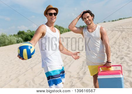 Join us. Positive delighted friends holding ball for volleyball and smiling while resting together on the beach
