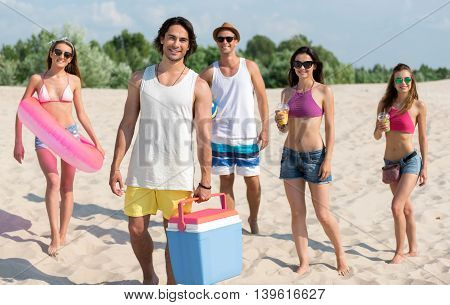 Lets make party. Positive delighted joyful friends smiling and standing on the beach while resting together