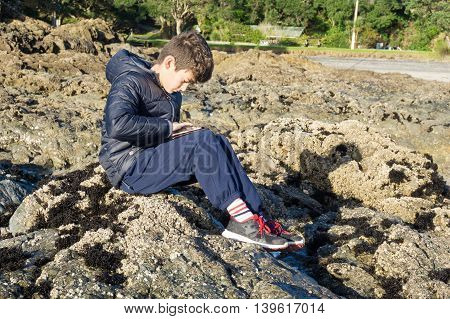 Boy on rocks playing on mobile device Waipu Cove