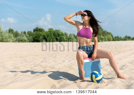 Where are you. Cheerful beautiful slim woman sitting on the beach and looking aside while resting