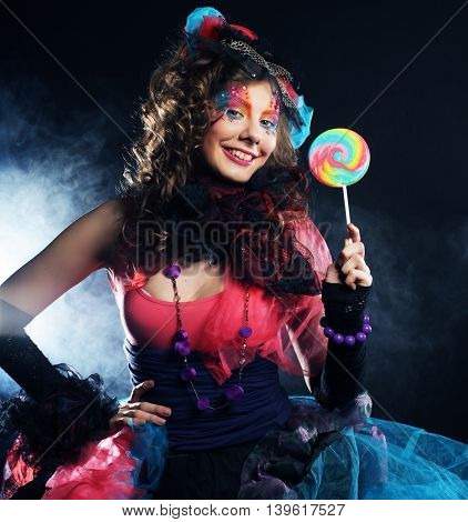 Girl with with creative make-up holds lollipop. Doll style. Studio shot.