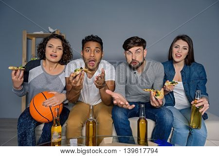 Friends forever. Cheerful group of friends watching football game on tv, isolated on grey background